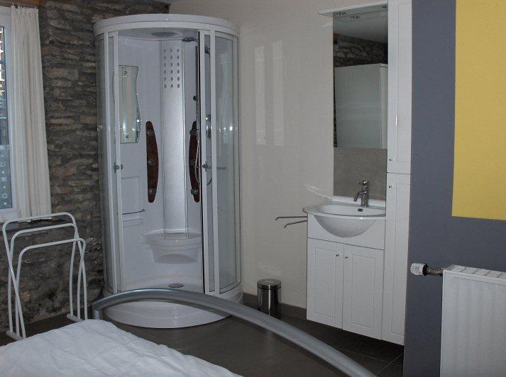 Slaapkamer op benedenverdieping met douche en wastafel